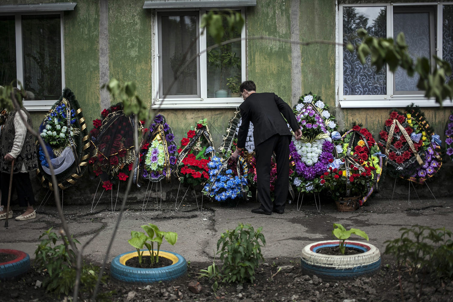 May 13, 2014. A man places flowers on the wall of Hyudych Vadim Yurievich's family home during his funeral, in the eastern Ukranian town of Krasnoarmisk.