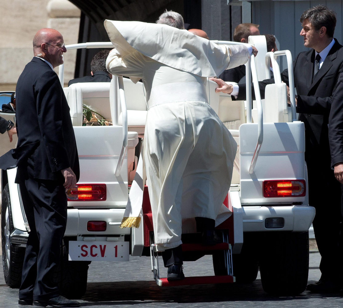 Pope Francis' cape flies up as he climbs the Popemobile at the end of his weekly Wednesday General Audience at St. Peter's Square in the Vatican City, May 14, 2014.