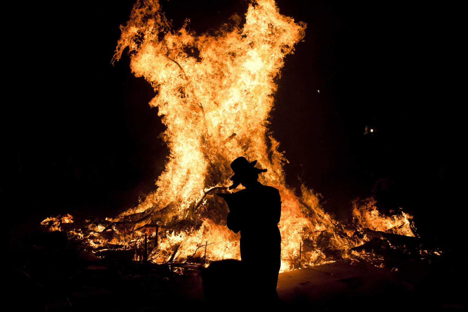 May 18, 2014. An Ultra Orthodox Jewish man stands near a bonfire in the neighborhood of Mea Shearim in Jerusalem, Israel during the commemoration the holy day of Lag Ba'Omer.