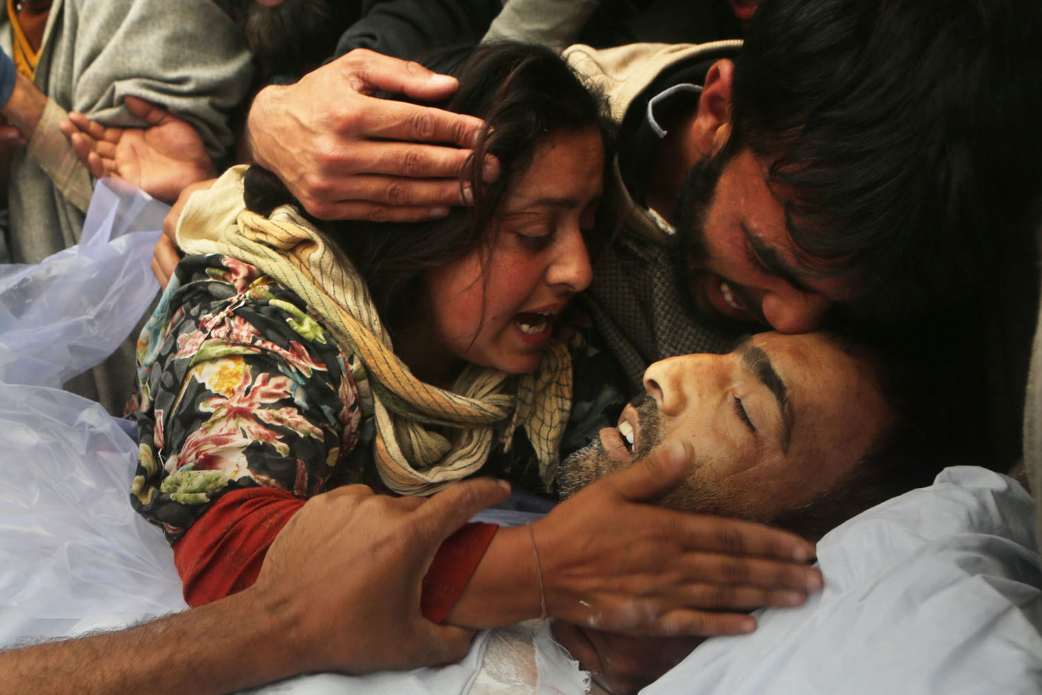 May 20, 2014. A woman hugs the body of her husband Mushtaq Ahmad Mir, an Indian Army soldier, during his funeral procession in Qazipora.