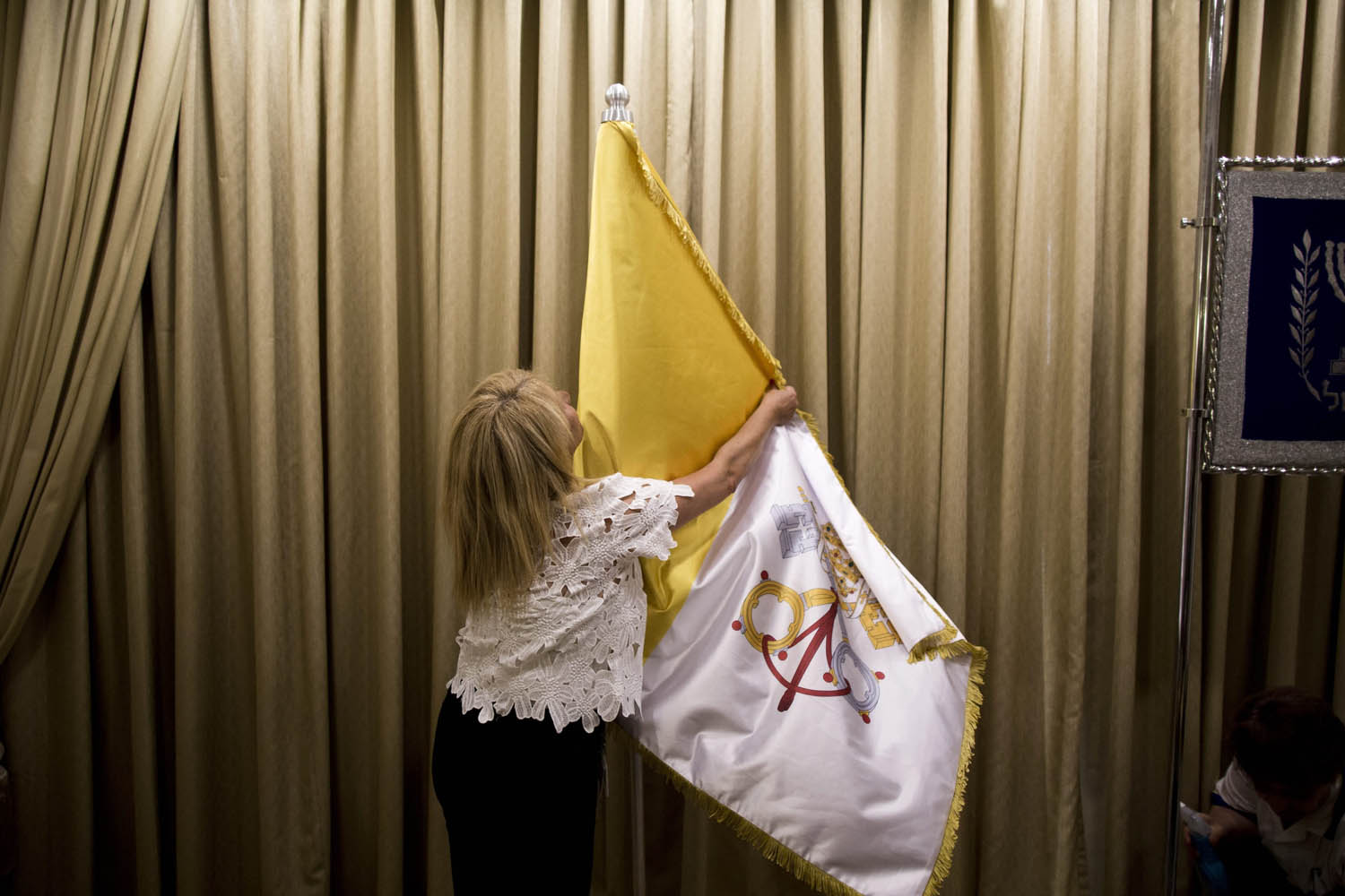 May 22, 2014. A worker at the Israeli President's Residence holds the flag of Vatican City in preparations for Pope Francis' visit to Jerusalem, Israel.