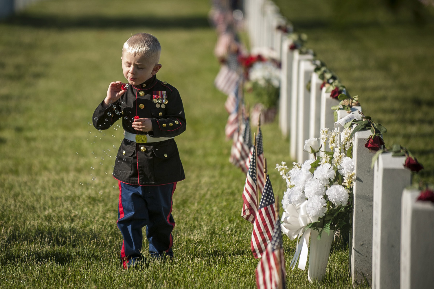 May 26, 2014. Christian Jacobs, 3, of Hertford, North Carolina, blows bubbles at the gravesite of his father, Marine Sgt. Christopher Jacobs, on Memorial Day at Arlington National Cemetery in Arlington, Virginia.