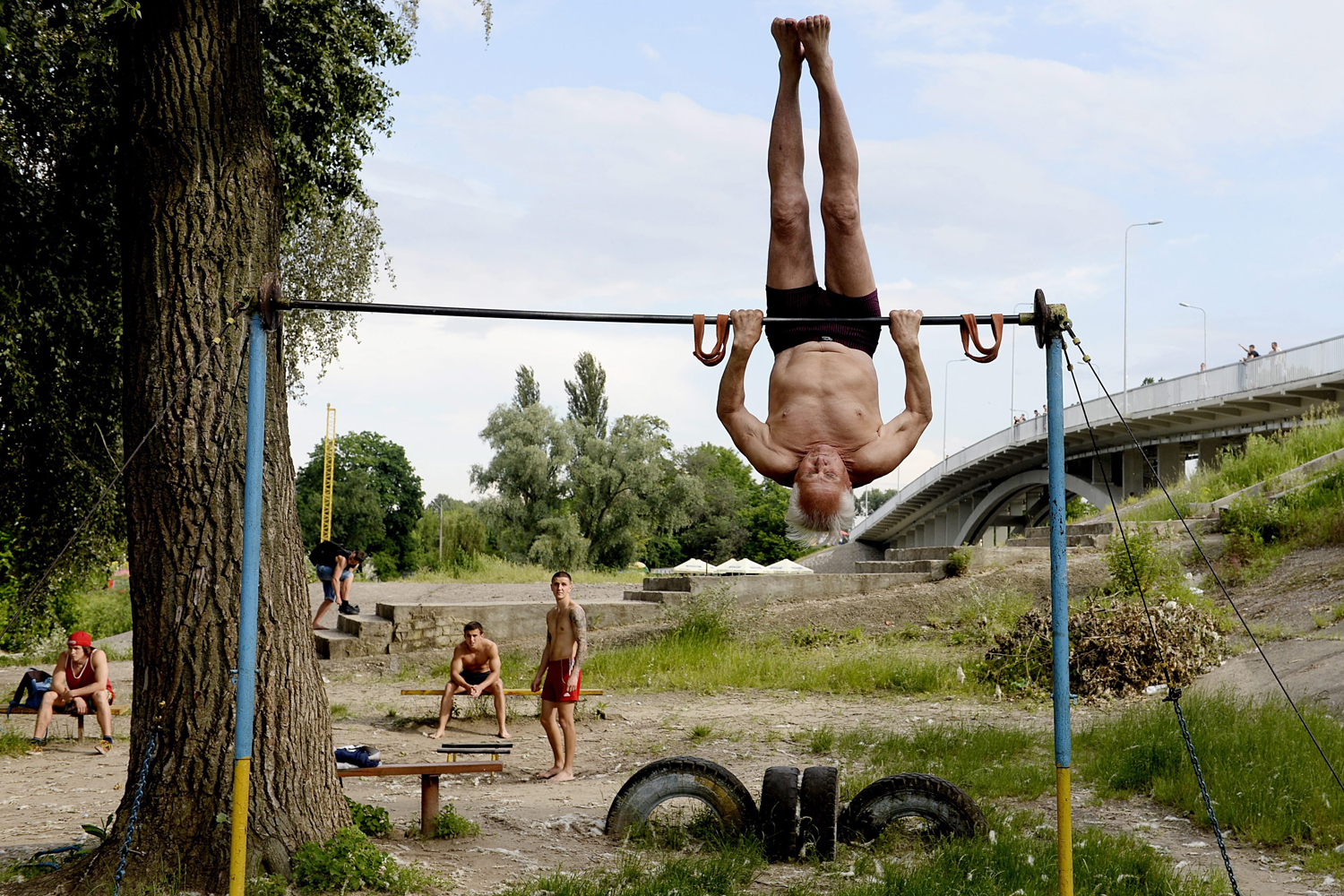 May 29, 2014. An elderly Ukrainian man exercises at the Kachalka outdoor gym on the banks of the river Dniper in Kiev, Ukraine,