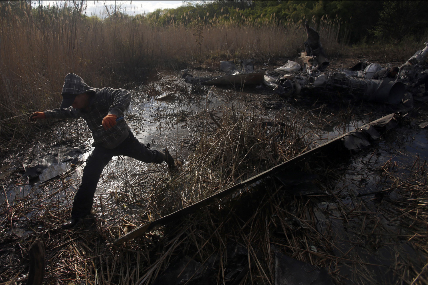 May 6, 2014. Local citizens collect parts of a downed Ukrainian military helicopter near the small town Raigorodok, outside Slovyansk, Ukraine.