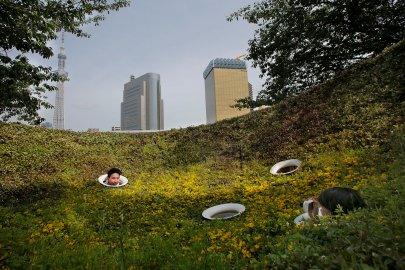A couple sticks their heads out of holes while taking a photograph at a public park in Tokyo, on May 19, 2014.