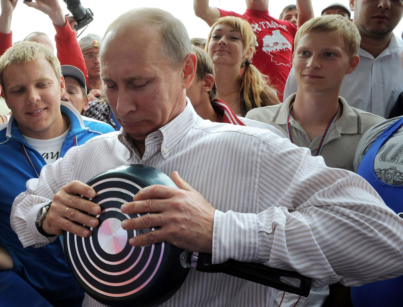 As pro-Kremlin youth activists look on, Putin attempts to bend a pan during his visit to a summer camp run by the Nashi youth group at Lake Seliger in the central Tver region of Russia, Aug. 1, 2011.