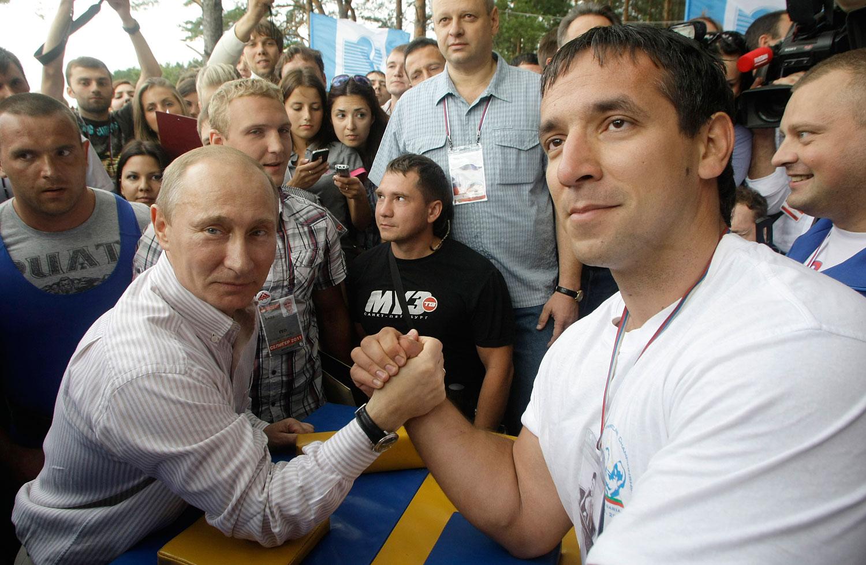 Putin, left, prepares to arm wrestle during his Nashi camp visit, Aug. 1, 2011.