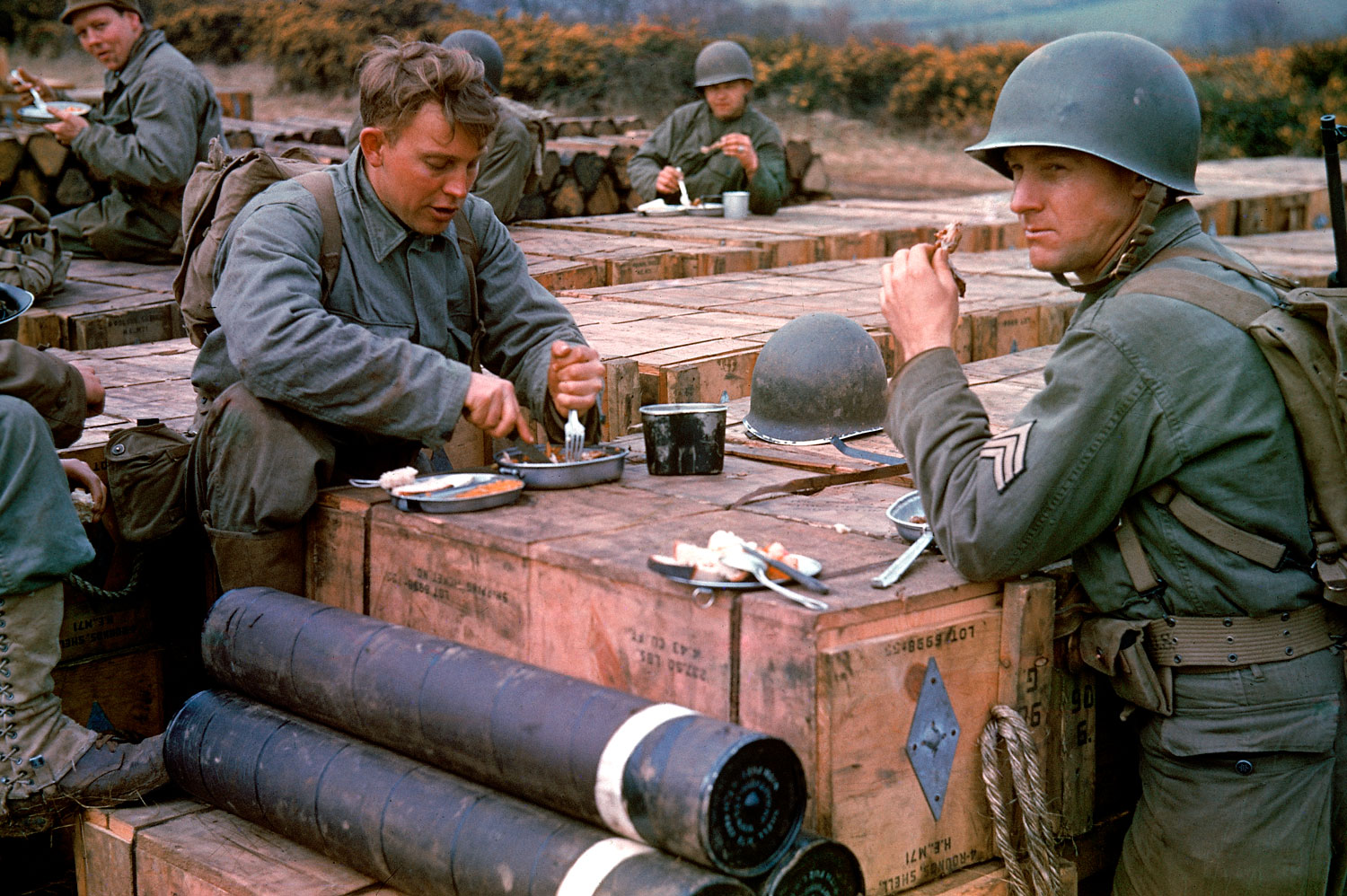 American combat engineers eat a meal atop boxes of ammunition stockpiled for the impending D-Day invasion, May 1944.