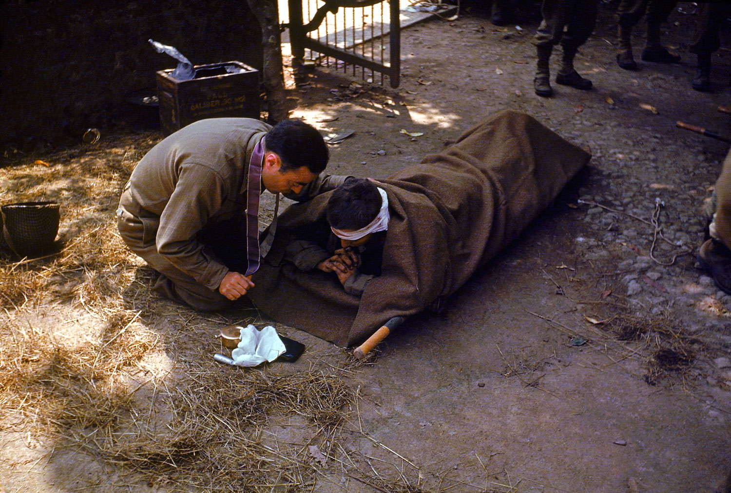 An American Army chaplain kneels next to a wounded soldier in order to administer the Eucharist and Last Rites, France, 1944.