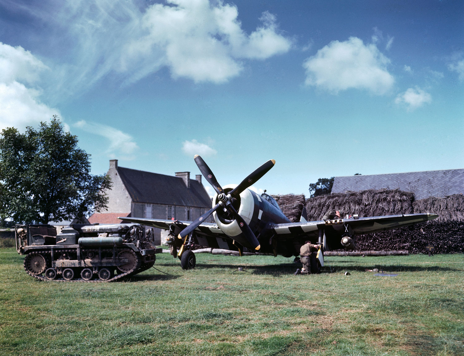 Maintenance work on an American P-47 Thunderbolt in a makeshift airfield in the French countryside, summer 1944.