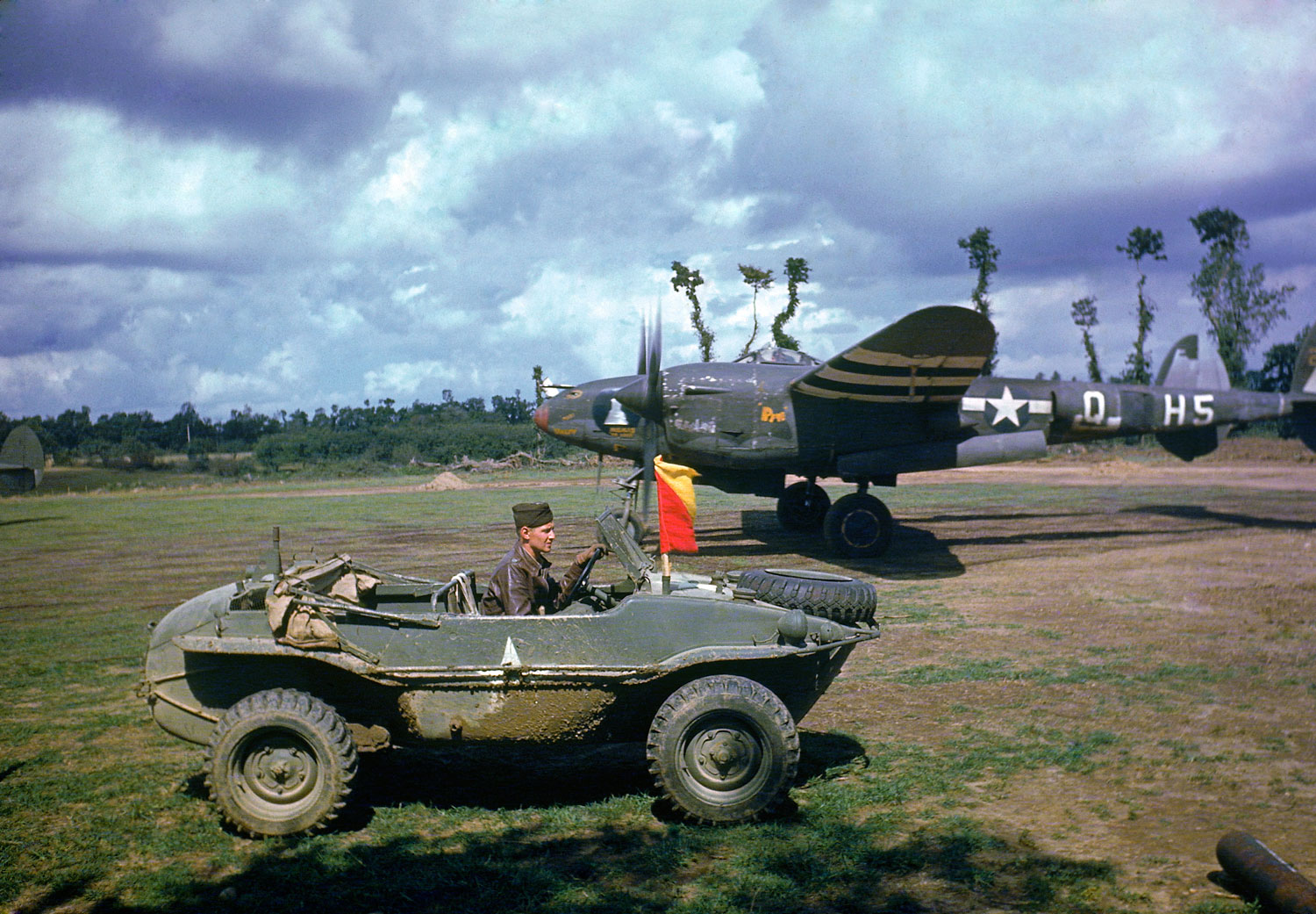 A P-38 fighter plane sits in the background as the pilot arrives in a captured German vehicle, France, 1944.