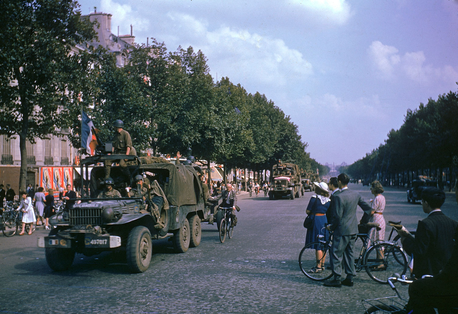 American Army trucks (note cyclist hitching a ride) parade down the Champs-Elysées the day after the liberation of Paris by French and Allied troops, August 1944.