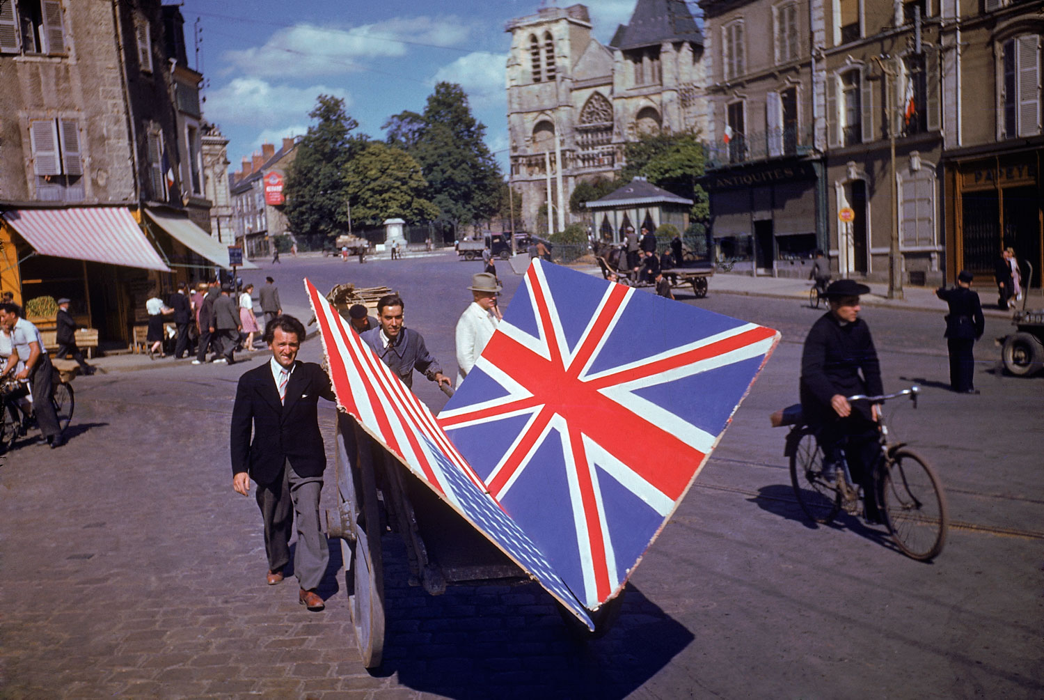 Frenchmen transport painted British and American flags for use in a parade, summer 1944.