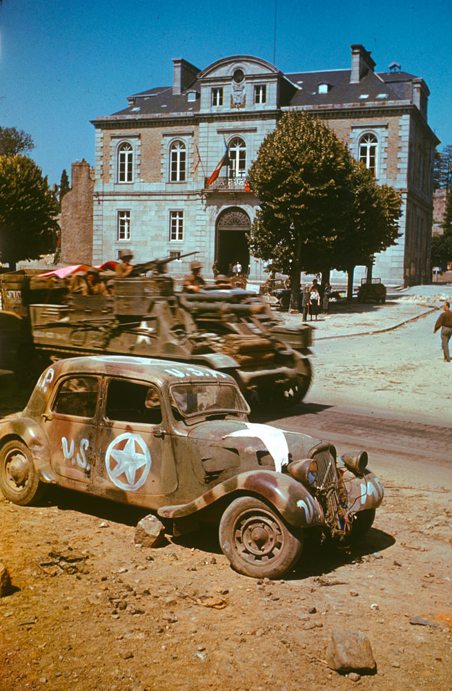 Armored vehicles on the move past civic buildings in Avranches, summer 1944.