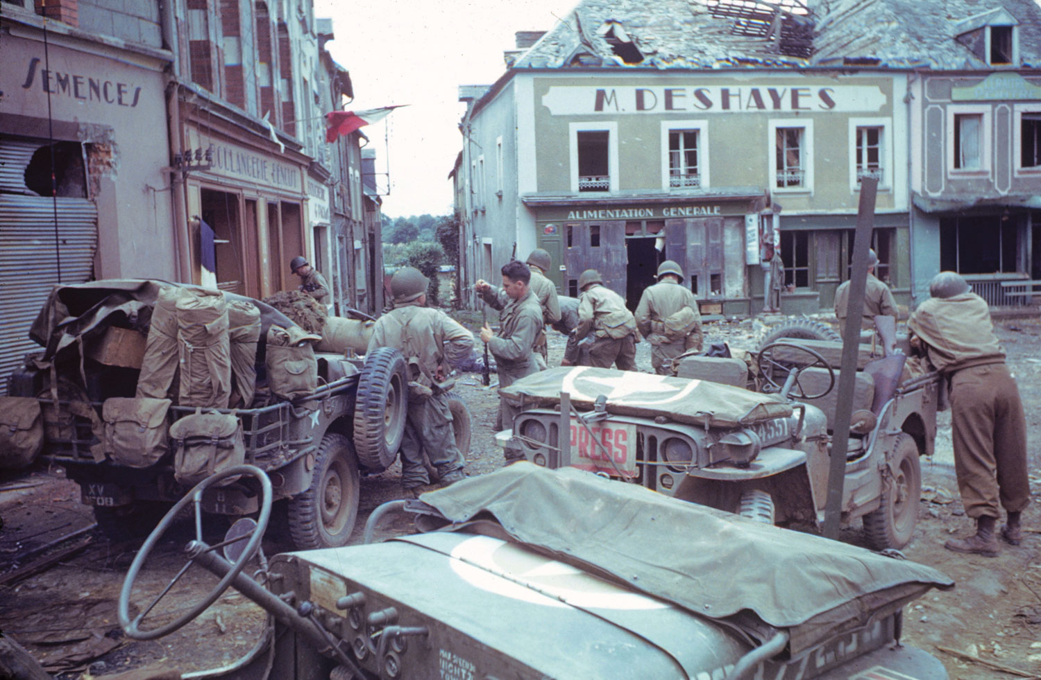 Jeeps (including a press vehicle) in the town square, Marigny (Manche), Normandy, 1944.