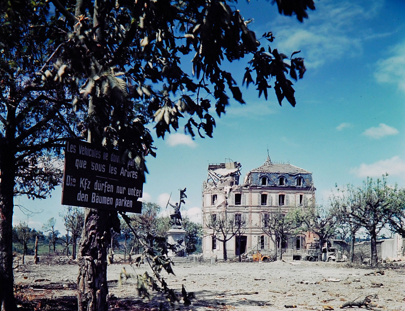 Ruined building and sign in French and German, northwestern France, summer 1944.