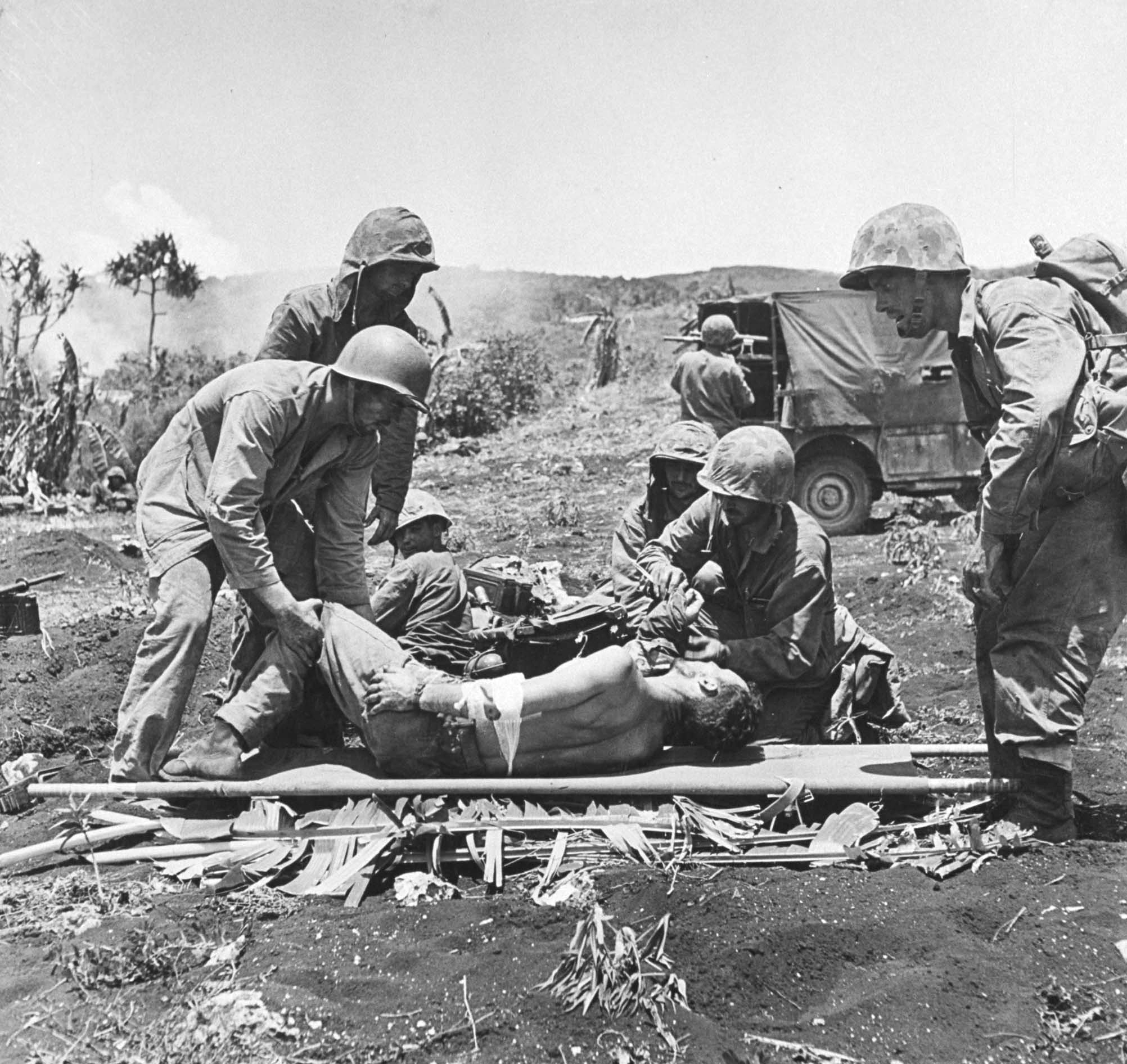 Marines tend to wounded comrades during the battle to take Saipan from the Japanese, 1944.
