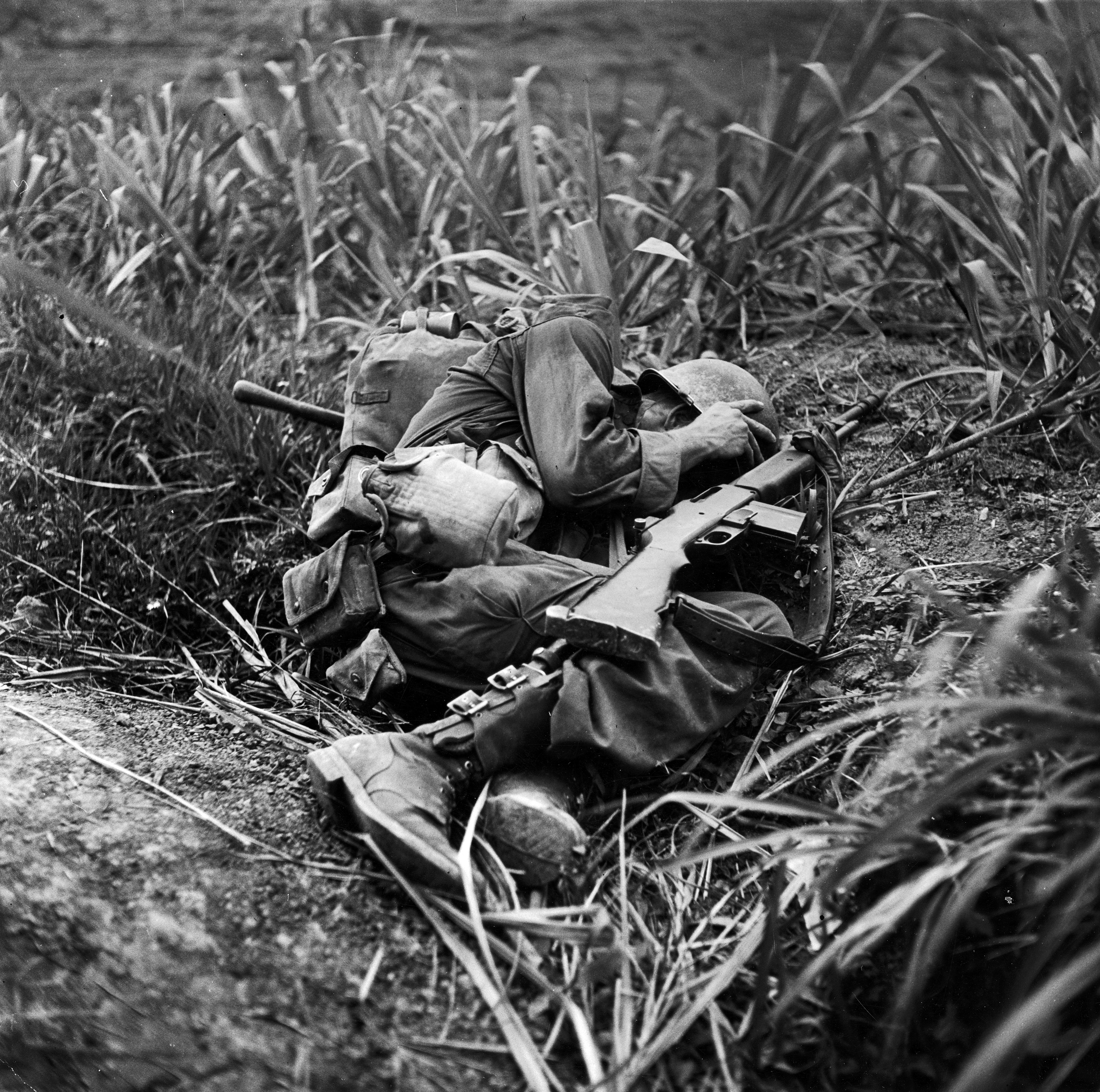 American infantryman Terry Moore takes cover as incoming Japanese artillery fire explodes nearby during the fight to take Okinawa, May 1945.