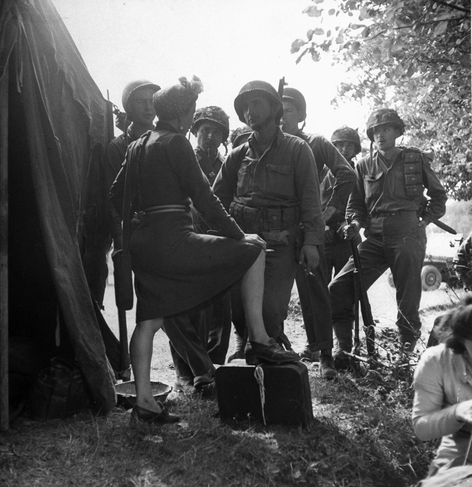 Caption from LIFE:  Stage-door Johnnies talk with French dancer at dressing tent. Most of dancers were Parisians. For soldiers in camp, the show's price of admission was paid by Army Special Services Fund.