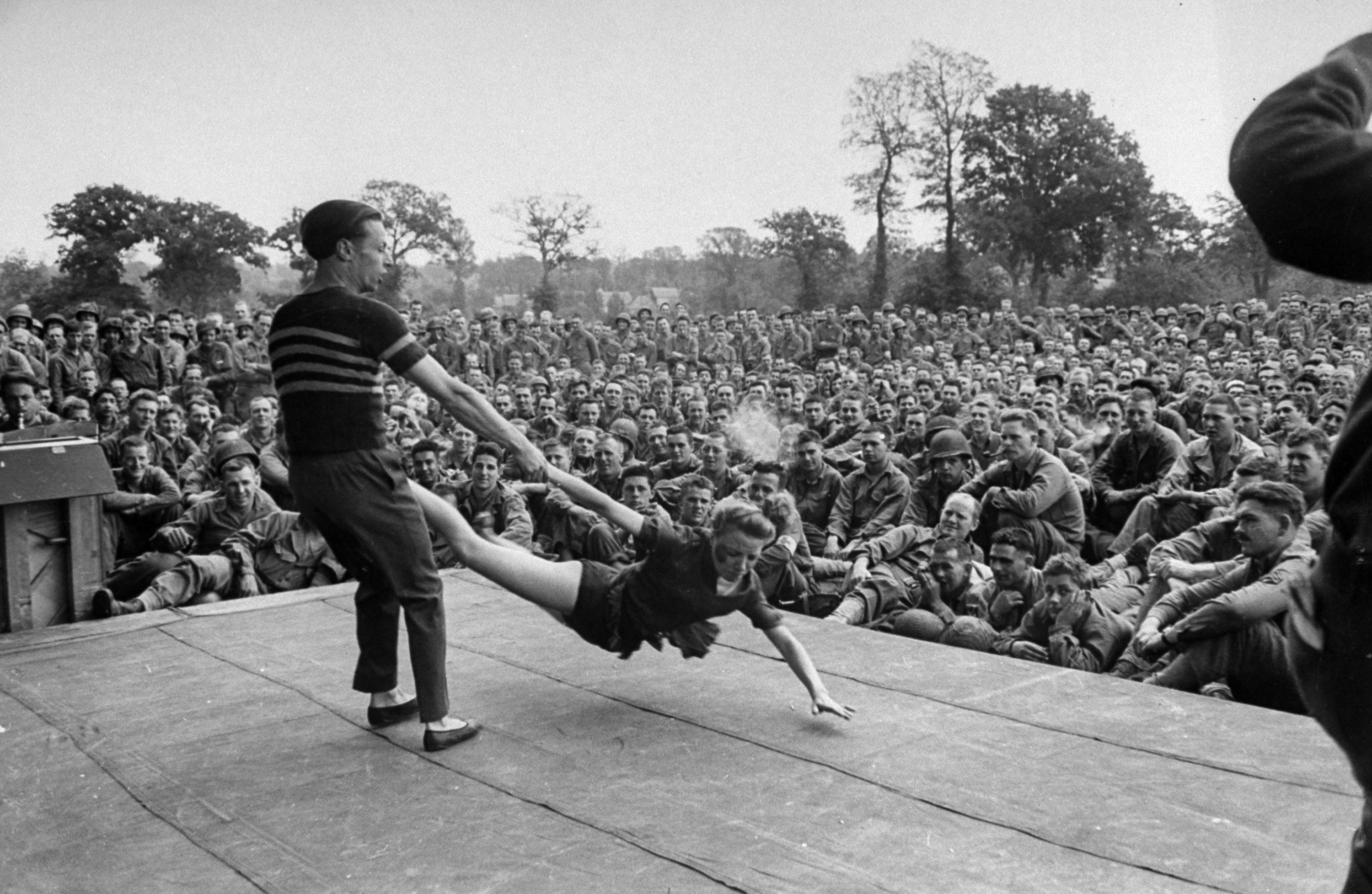 Caption from LIFE:  Dancer skims stage dangerously as she is swung by male partner. The men at show were from 20th Division. Its commanding general, Major Gen. Charles H. Gerhardt, also attended.