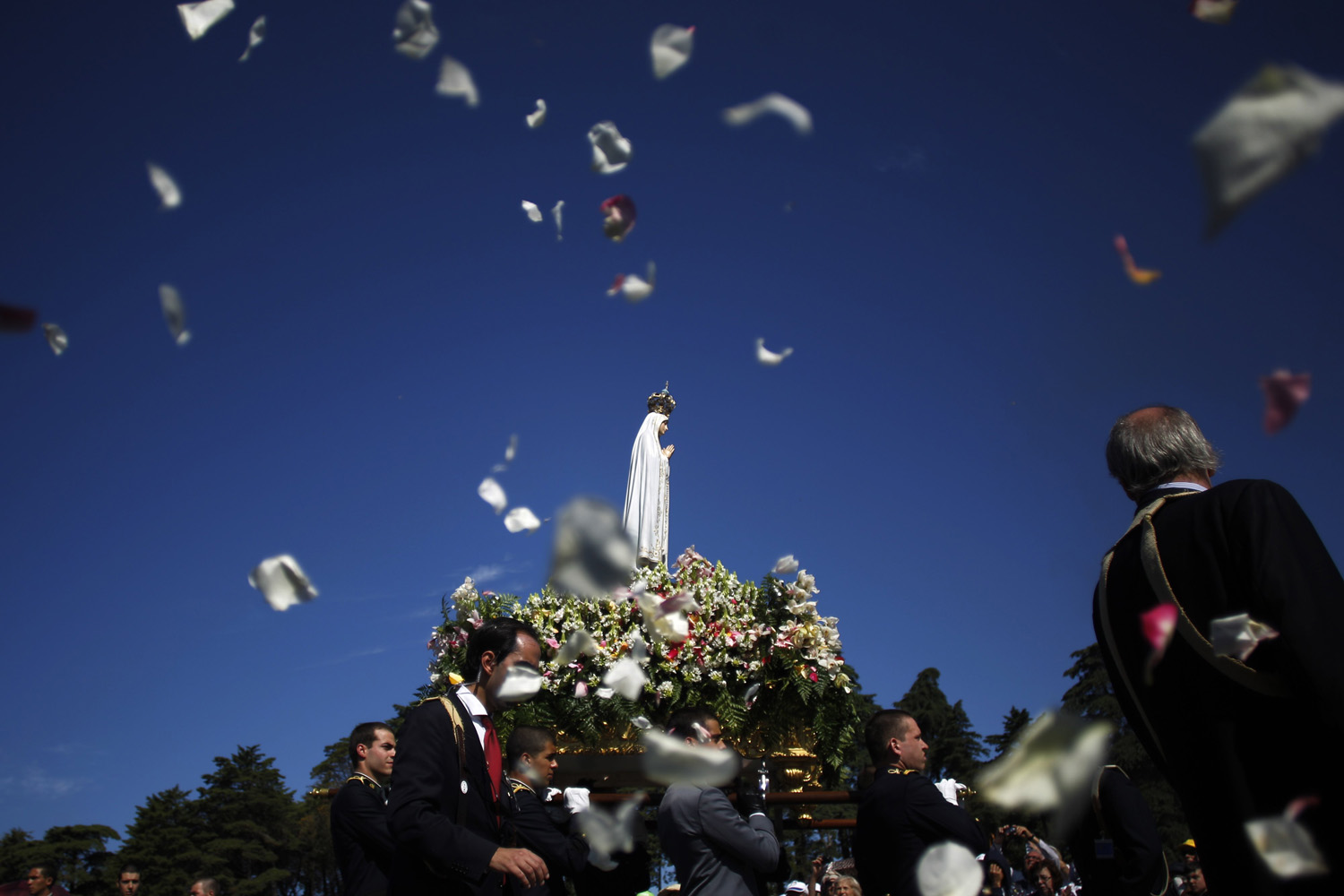 May 13, 2014. Worshipers throw flower petals to the statue of  Our Lady of Fatima at the Our Lady of Fatima shrine, in Fatima, centre Portugal.