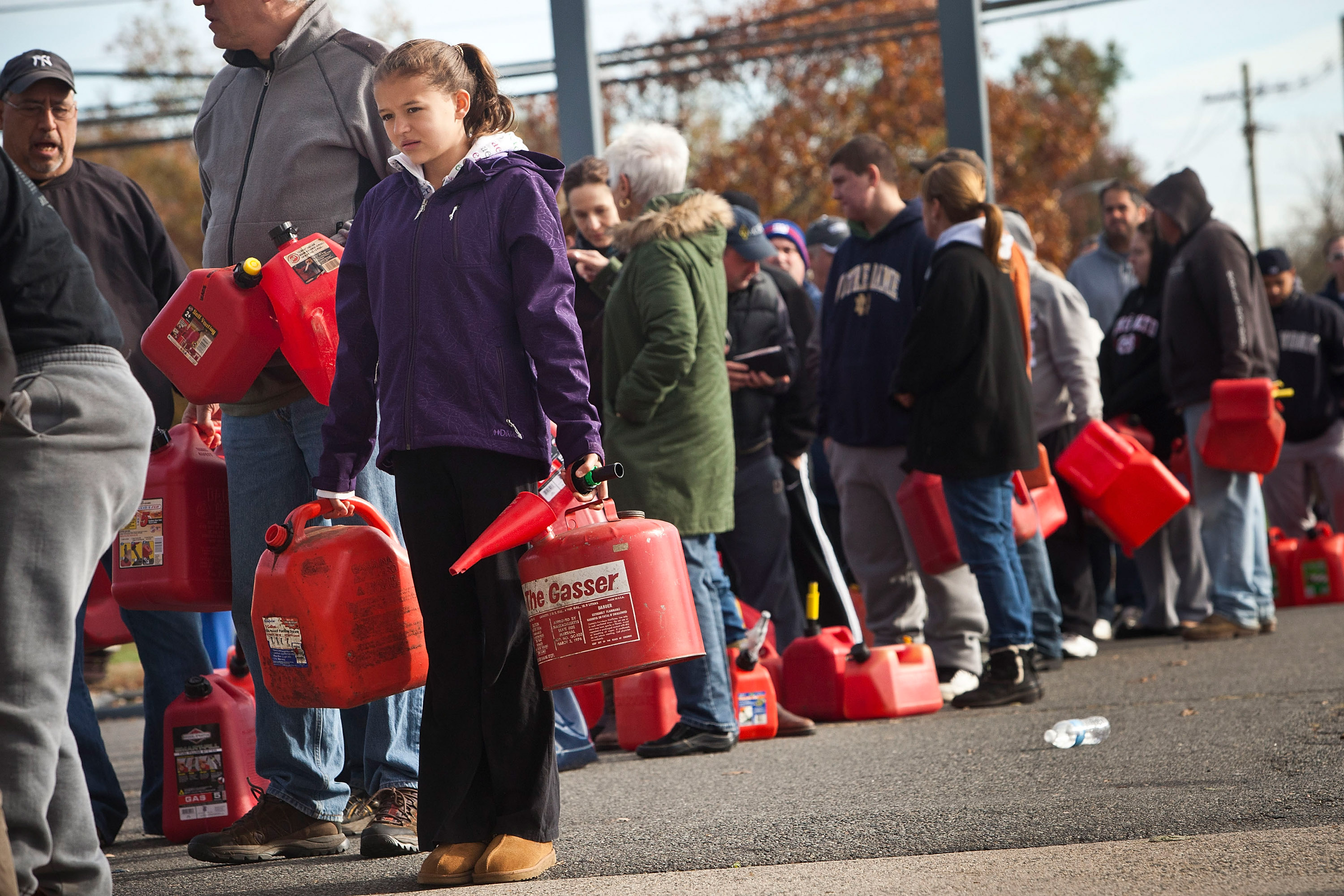 A girl holds jerry cans while waiting in line at a gas station in Hazlet township, N.J., Nov. 1, 2012.