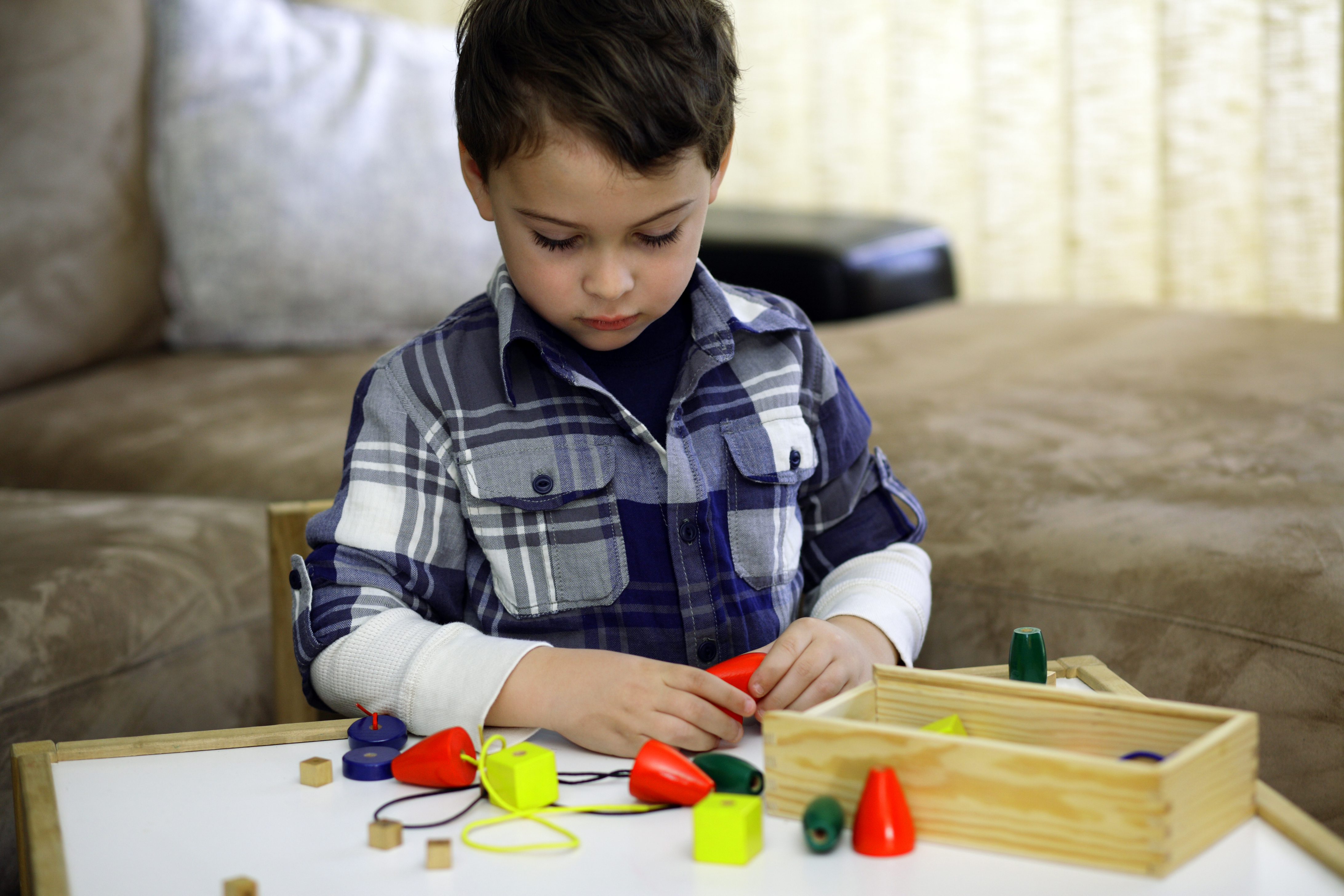 Young boy with autism selecting the right combination of beads to string together. Large beads allow the boy to better manipulate the objects to develop fine motor skills.