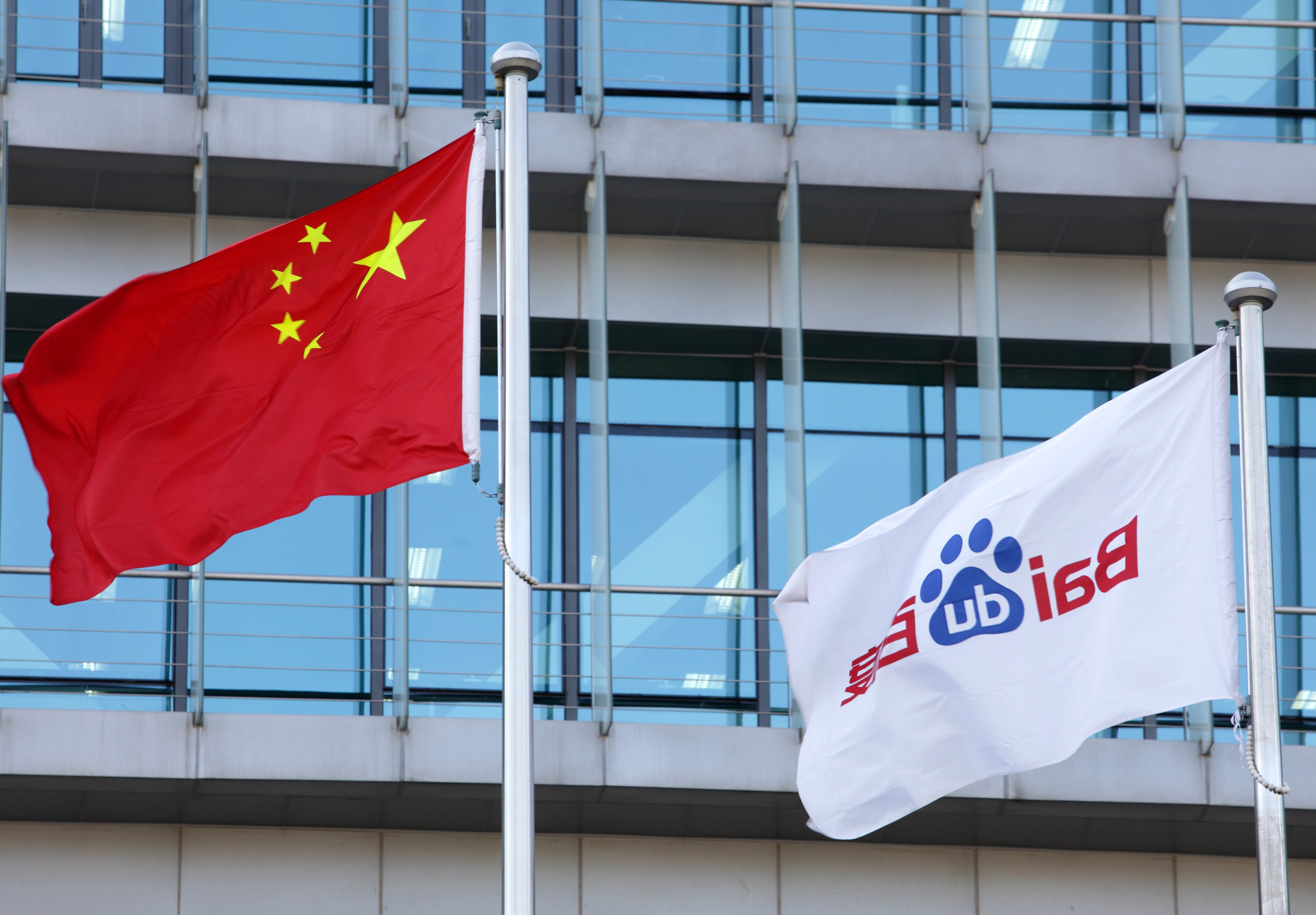 China's national flag, left, and Baidu Inc.'s corporate flag fly outside Baidu's headquarters in Beijing, China, on Monday, Nov. 12, 2012.