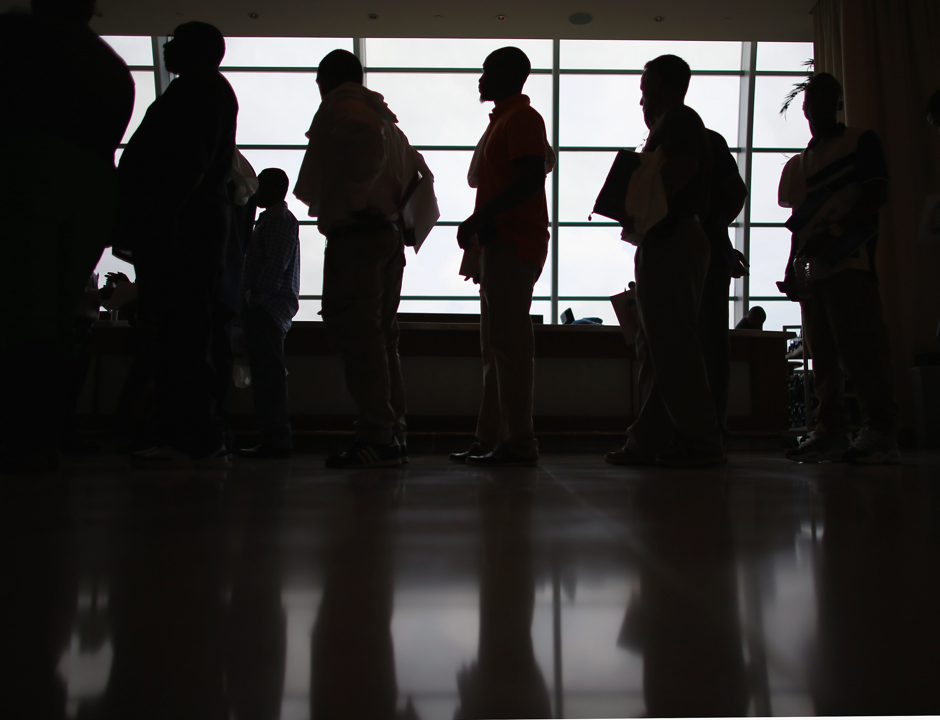 People looking for work stand in line to apply for a job during a job fair at the Miami Dolphins Sun Life stadium on May 2, 2013 in Miami, Florida.