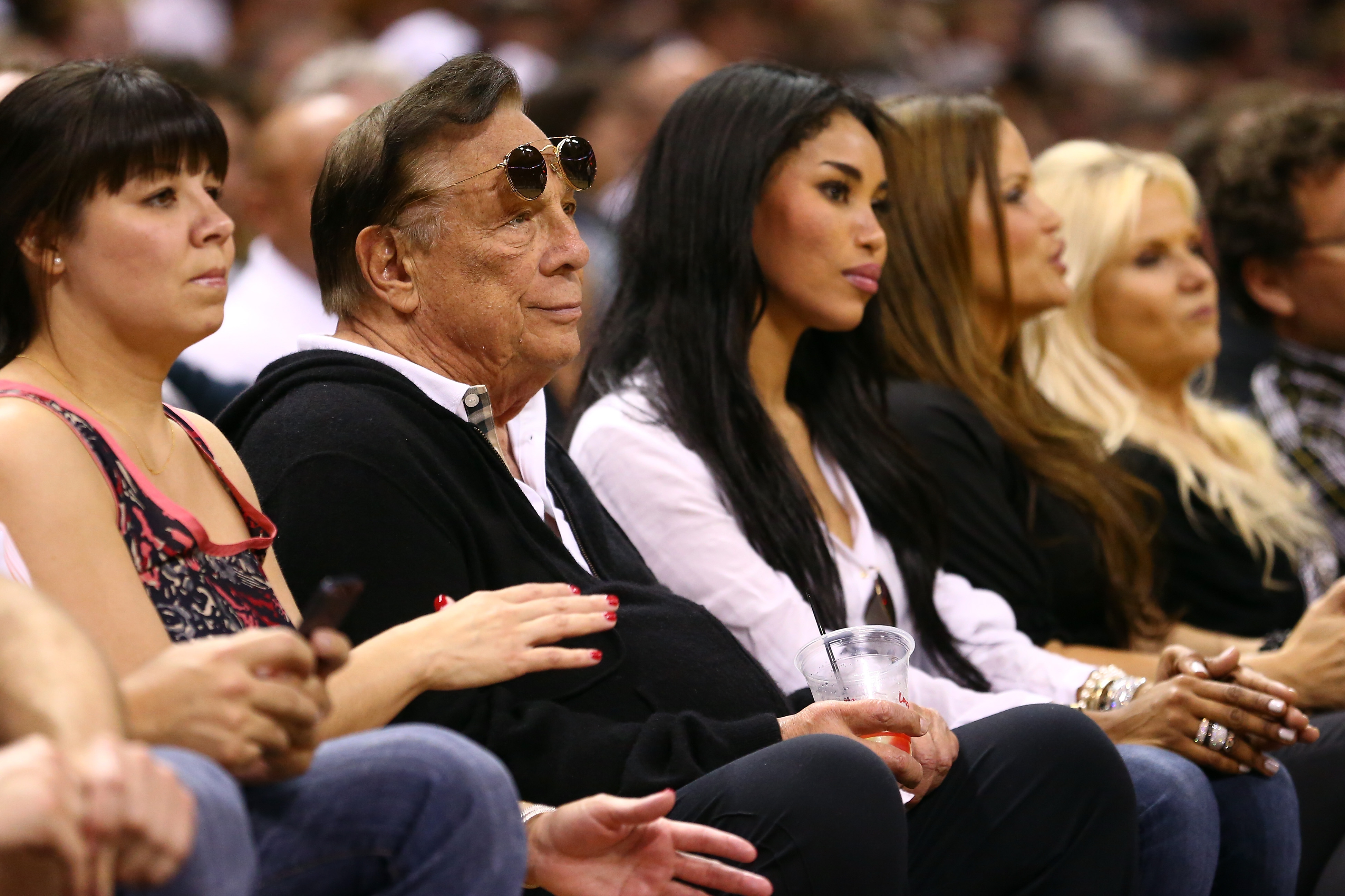 Team owner Donald Sterling (center) of the Los Angeles Clippers and V. Stiviano (second from right) watch the San Antonio Spurs play against the Memphis Grizzlies in San Antonio on May 19, 2013.