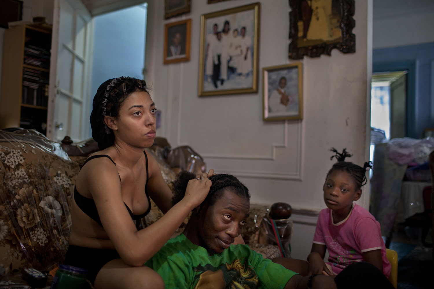 August 8, 2013. East Flatbush, Brooklyn. Sarah braids her brother's hair in their mother's home as her niece looks on.