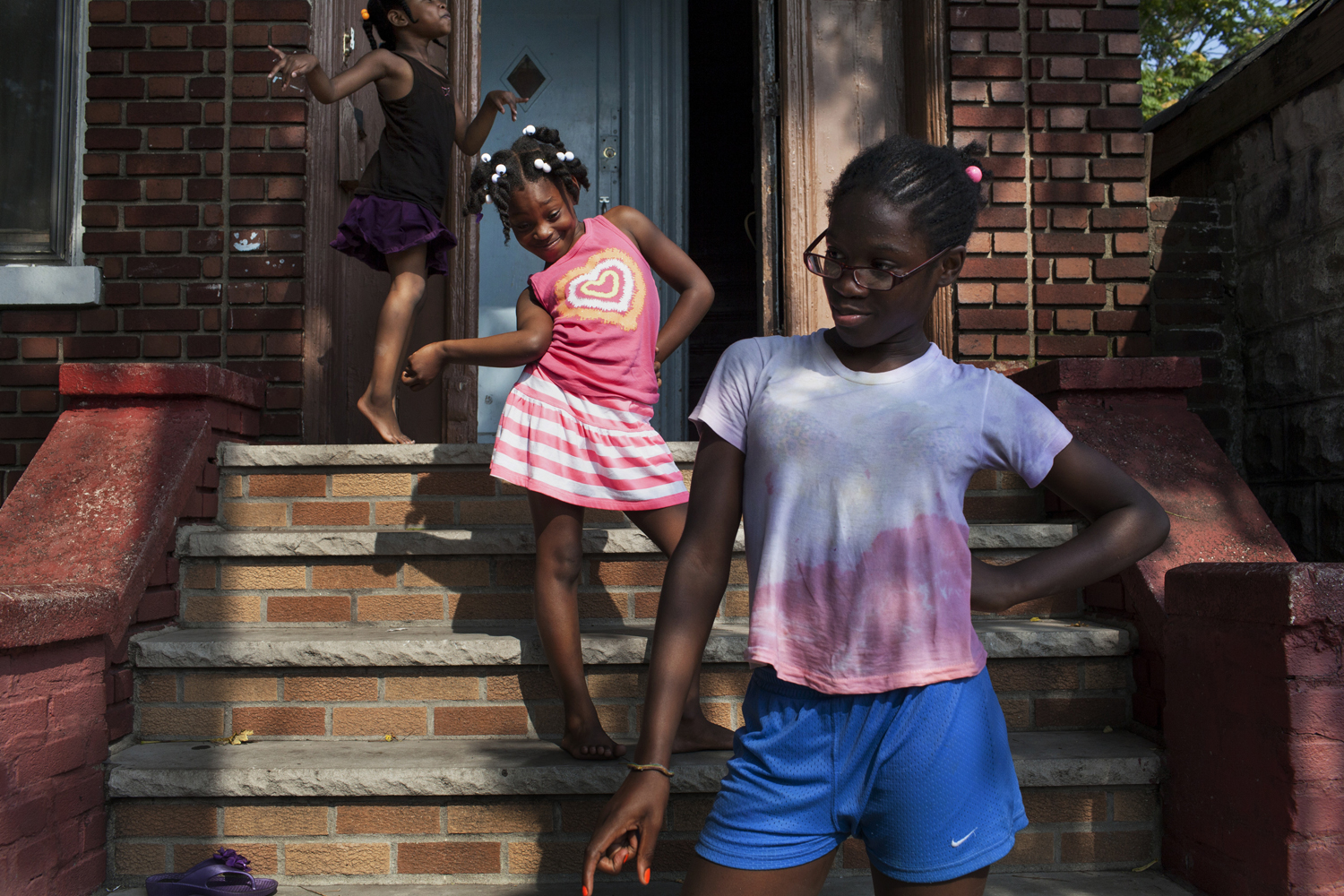 August 21, 2013. Flatbush, Brooklyn. Sarah's niece and her friends strike poses on the stoop of Sarah's home on a summer afternoon.  Dancehall dancers often site their dance abilities as part of their Caribbean heritage. Young girls start to learn some of the less suggestive dance moves in a dance hall queen's repertoire very young, but Sarah's niece giggle and exclaims  We're too young!  when asked if she can dance like her auntie. Two months later, Sarah will be shot in the foot just a few feet from this stoop.