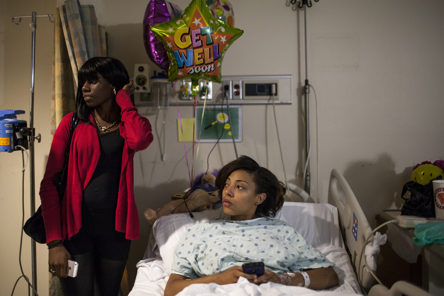October 2, 2013. Sarah, medicated on high doses of pain killers, lies in a hospital bed surrounded by friends and get well soon gifts, the day after she was shot in the foot outside her family's home in East Flatbush. She heard shots and started to run, but a bullet ricocheted off the sidewalk  and lodged in her heel. It had to be surgically removed.