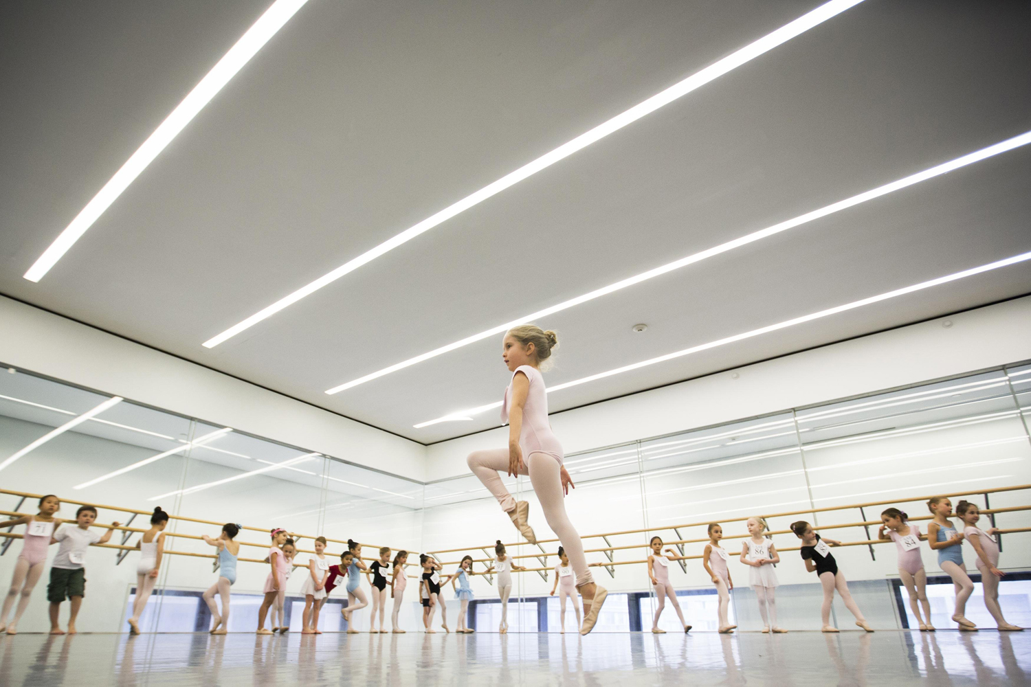 Children watch as a girl dances during an audition for the School of American Ballet in New York on April 25, 2014.