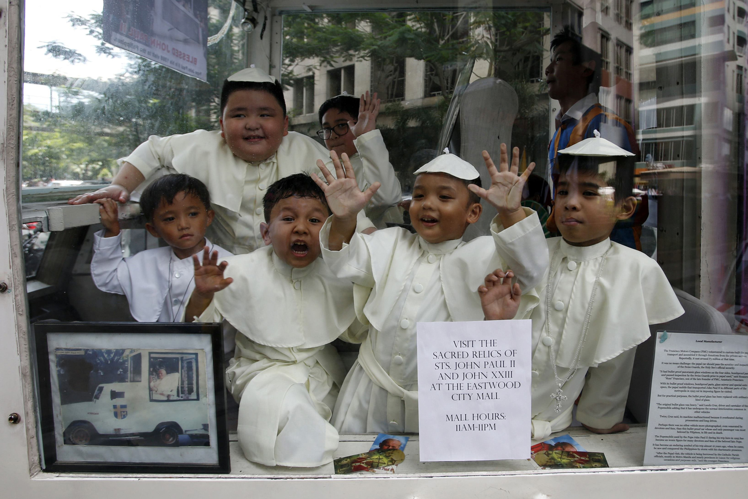 Children wearing Pope's cassocks ride a Popemobile that was used by Pope John Paul II in his 1995 visit to Manila, during a parade in Quezon city, Metro Manila on April 27, 2014.