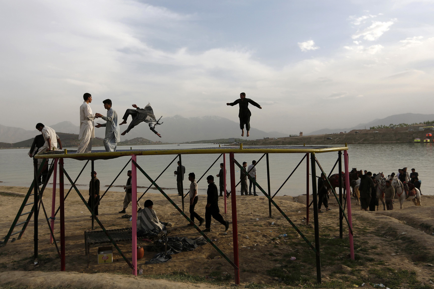 Afghans play on a trampoline along Qargha Lake, on the outskirts of Kabul on April 28, 2014.