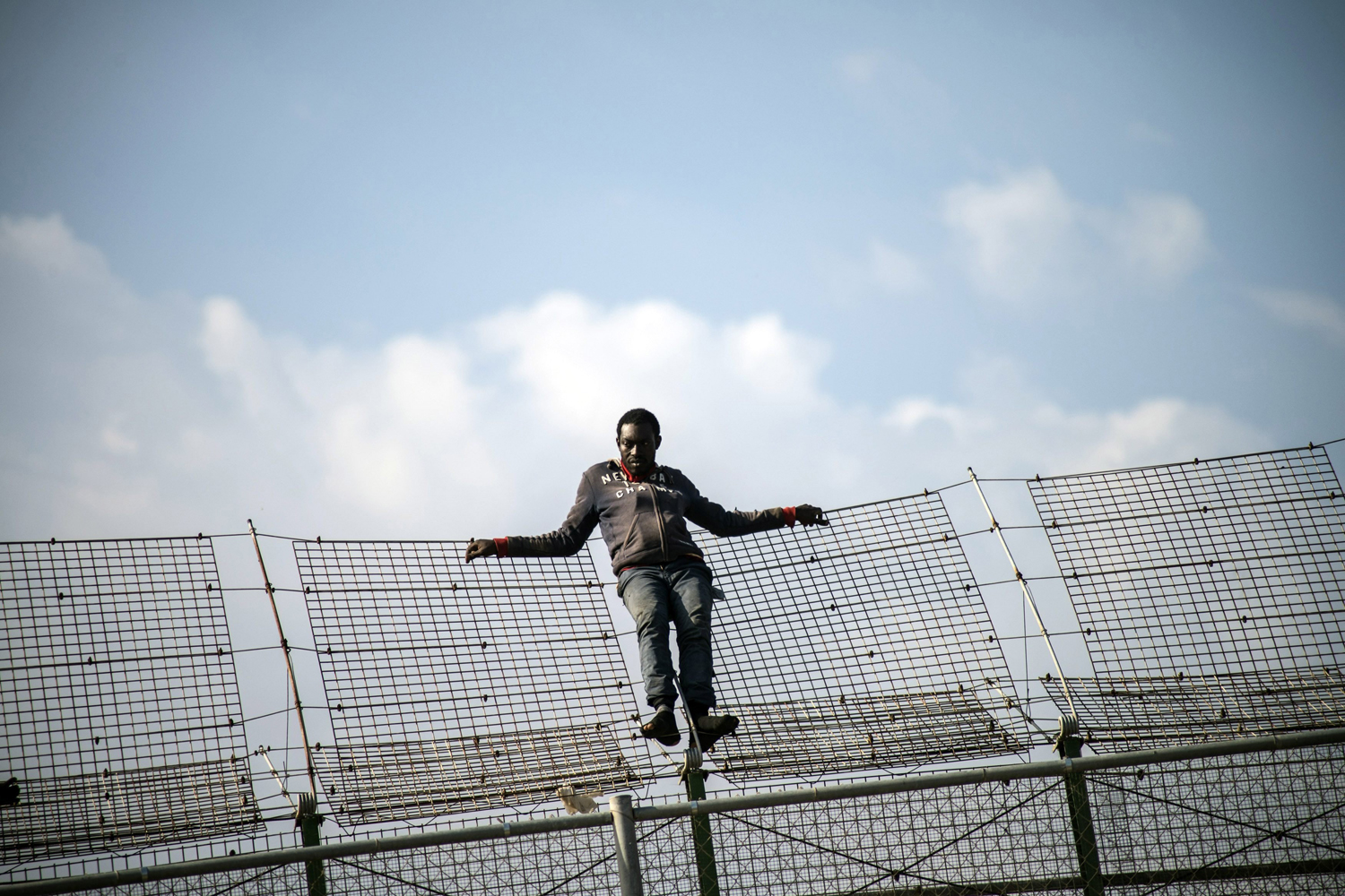 May 1, 2014.  An African migrant rests on a border fence covered in razor wire during a latest attempt to cross into Spanish territory, between Morocco and Spain's north African enclave of Melilla.