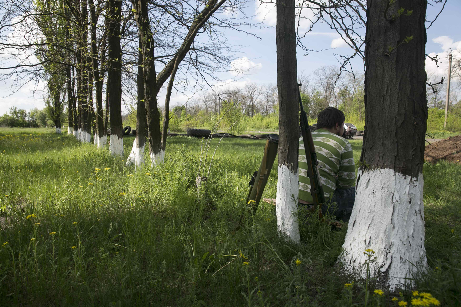 May 1, 2014. A pro-Russian man leans on a tree with a rifle and rocket launcher near him at a checkpoint near the town of Slaviansk, east Ukraine