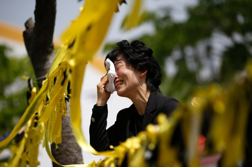 A mourner cries next to yellow ribbons dedicated to missing and dead passengers of sunken passenger ship Sewol, after paying tribute at the official memorial altar in Ansan