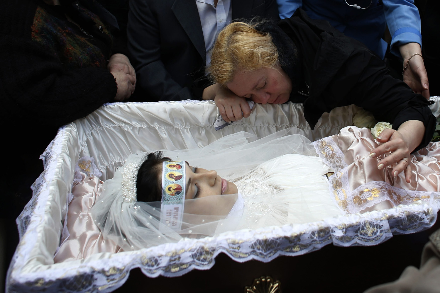 May 5, 2014. The mother of 21-year-old nurse Yulia Izotova mourns at her funeral in Kramatorsk, eastern Ukraine.
