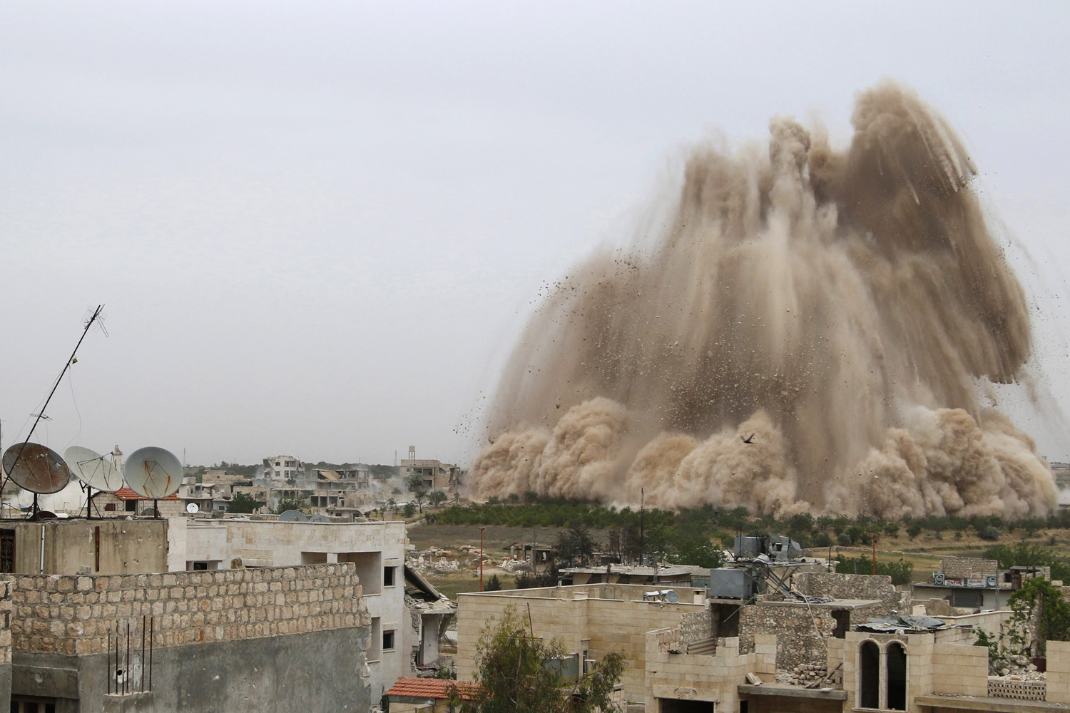 May 5, 2014. Debris rises in what Free Syrian Army fighters and Islamic rebels said was an operation to strike Al-Sahaba checkpoint, which is considered a gateway to Al-Dayf valley, and remove forces loyal to Syria's President Bashar Al-Assad in Maarat Al-Nouman, Idlib province.