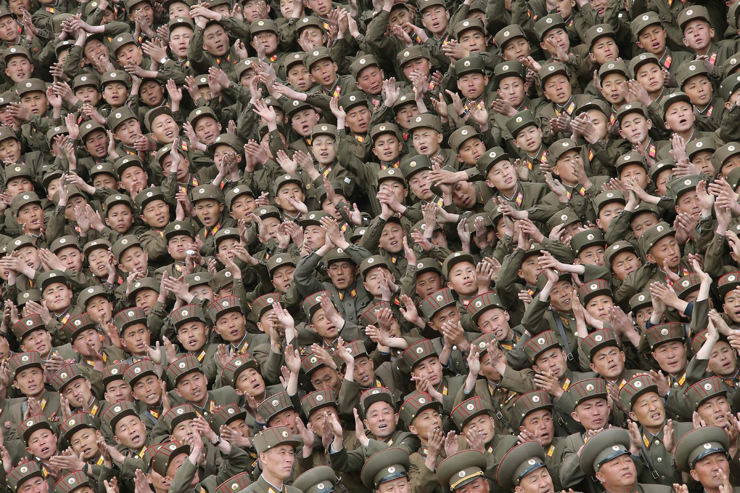 May 6, 2014. Soldier-builders of KPA Units 966, 462, 101, 489, who took part in building the workers' hostel of Kim Jong Suk Pyongyang Textile Mill, applaud during a photo session with North Korean leader Kim Jong Un.