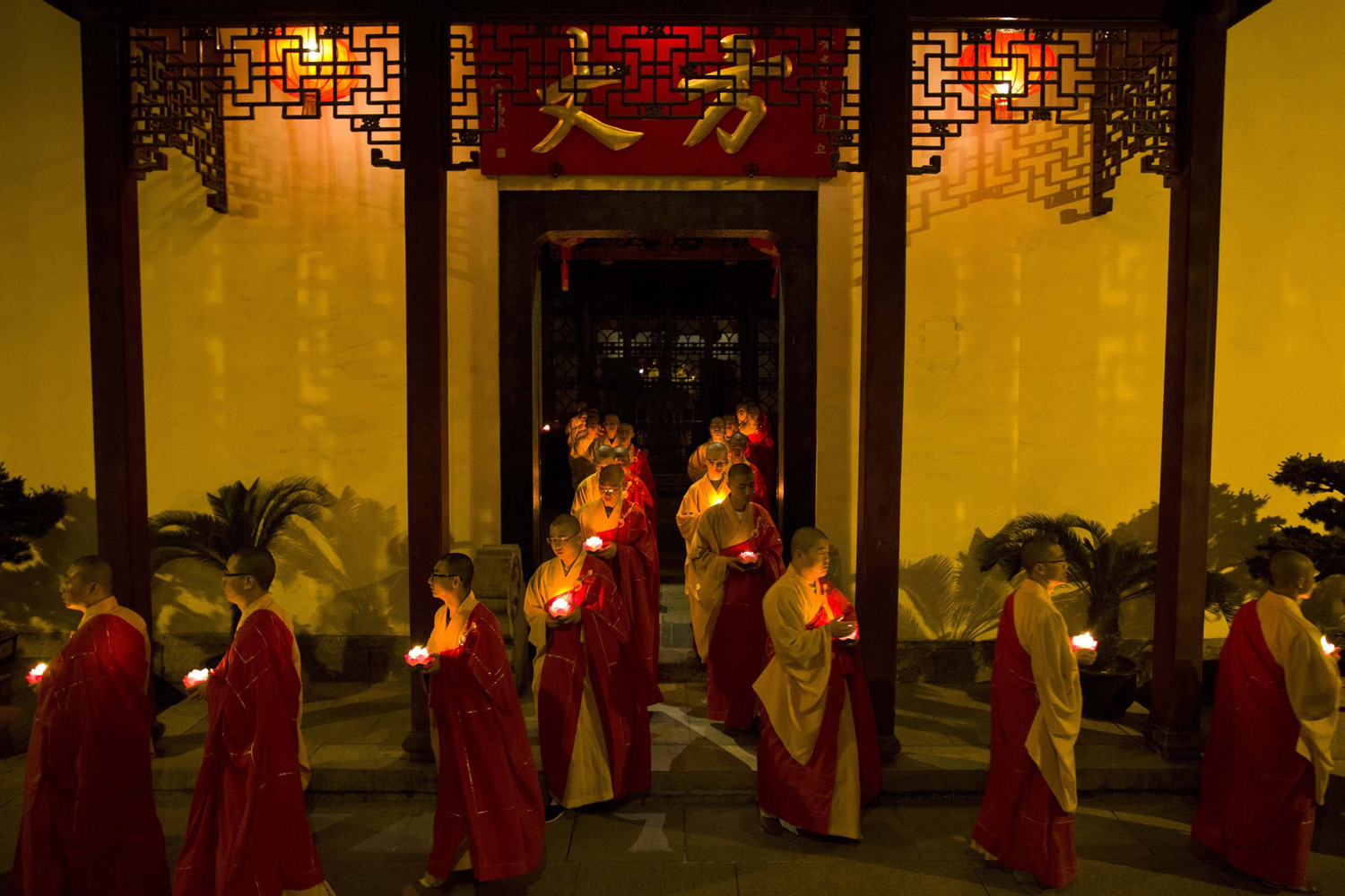 May 6, 2014. Monks hold candles as they pray during a ceremony to celebrate Buddha's birthday at the Yufo Temple in Shanghai.
