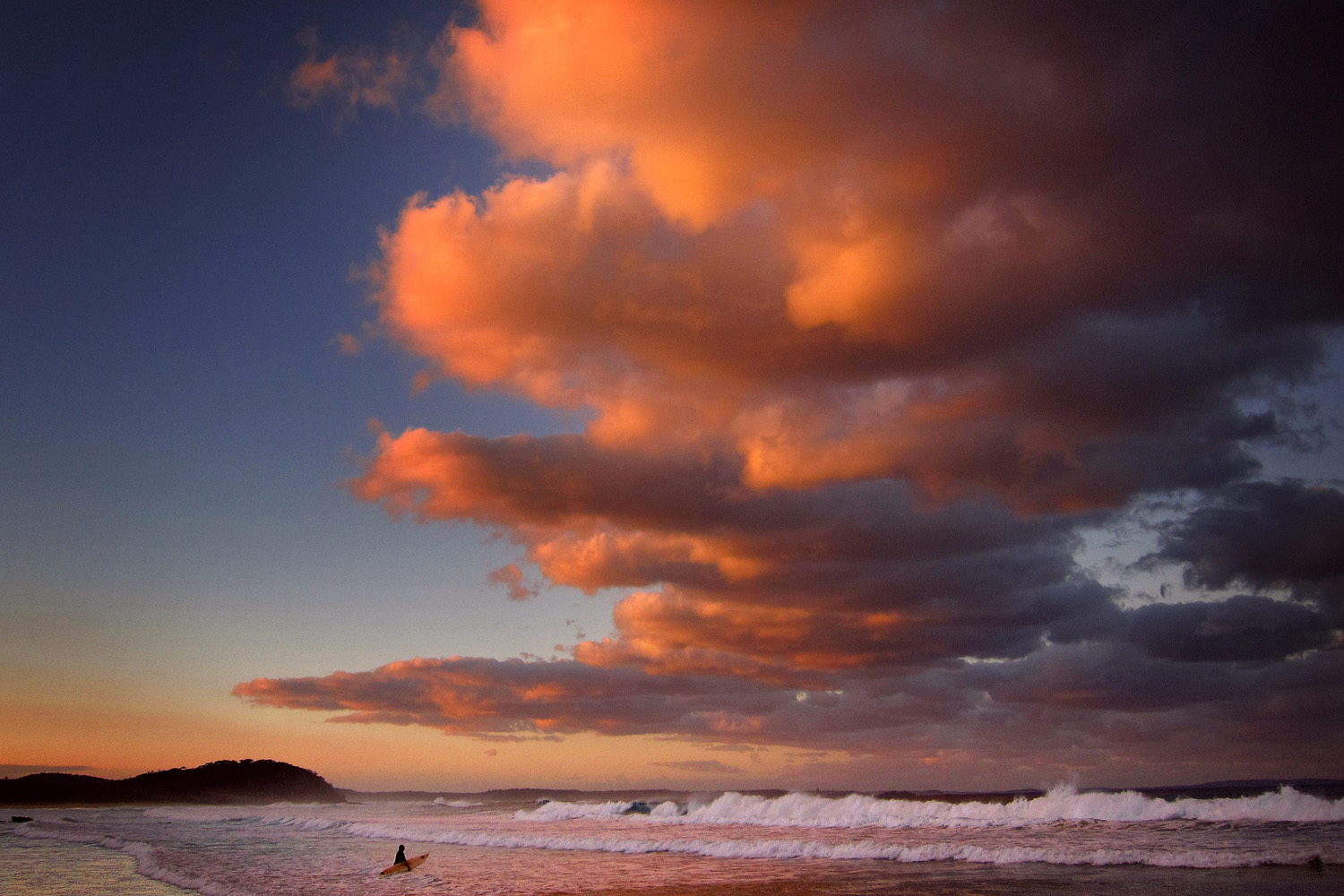 A surfer holding her board wades through the surf as clouds above are lit by the setting sun at Mollymook Beach on the south coast of New South Wales May 8, 2014.