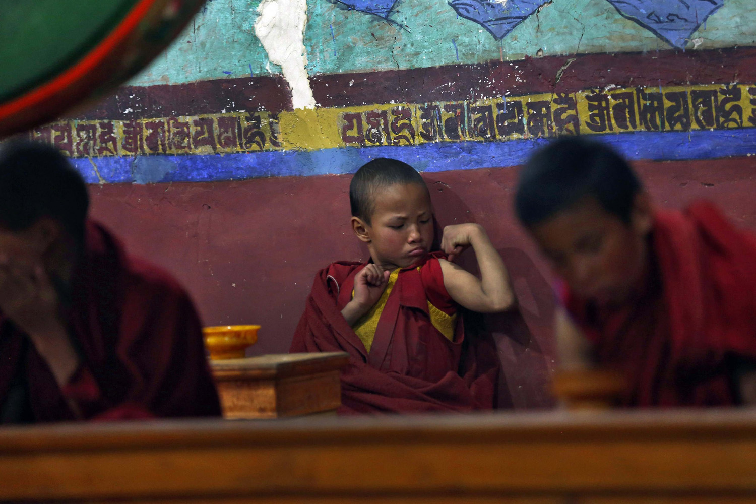 A young Buddhist monk flexes his muscles during morning prayers at Thikse Monastery in Ladakh, Indian administered Kashmir on May 7, 2014.