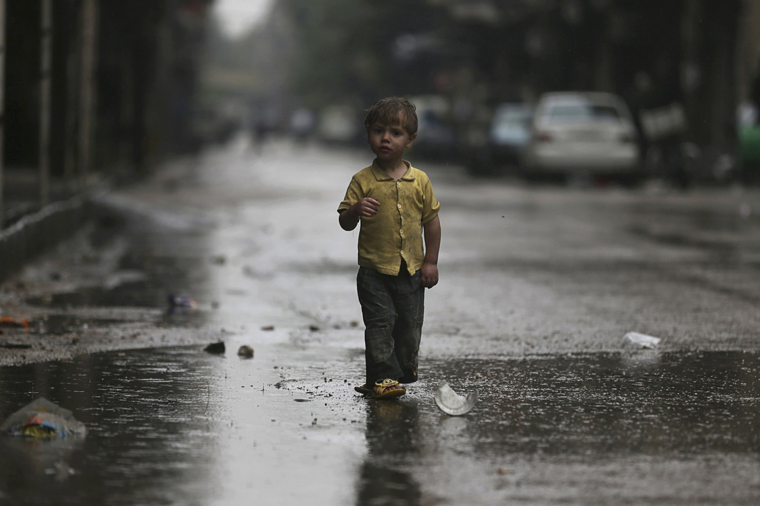 May 8, 2014. A child walks along a street during rainy weather in the Duma neighbourhood of Damascus, Syria.