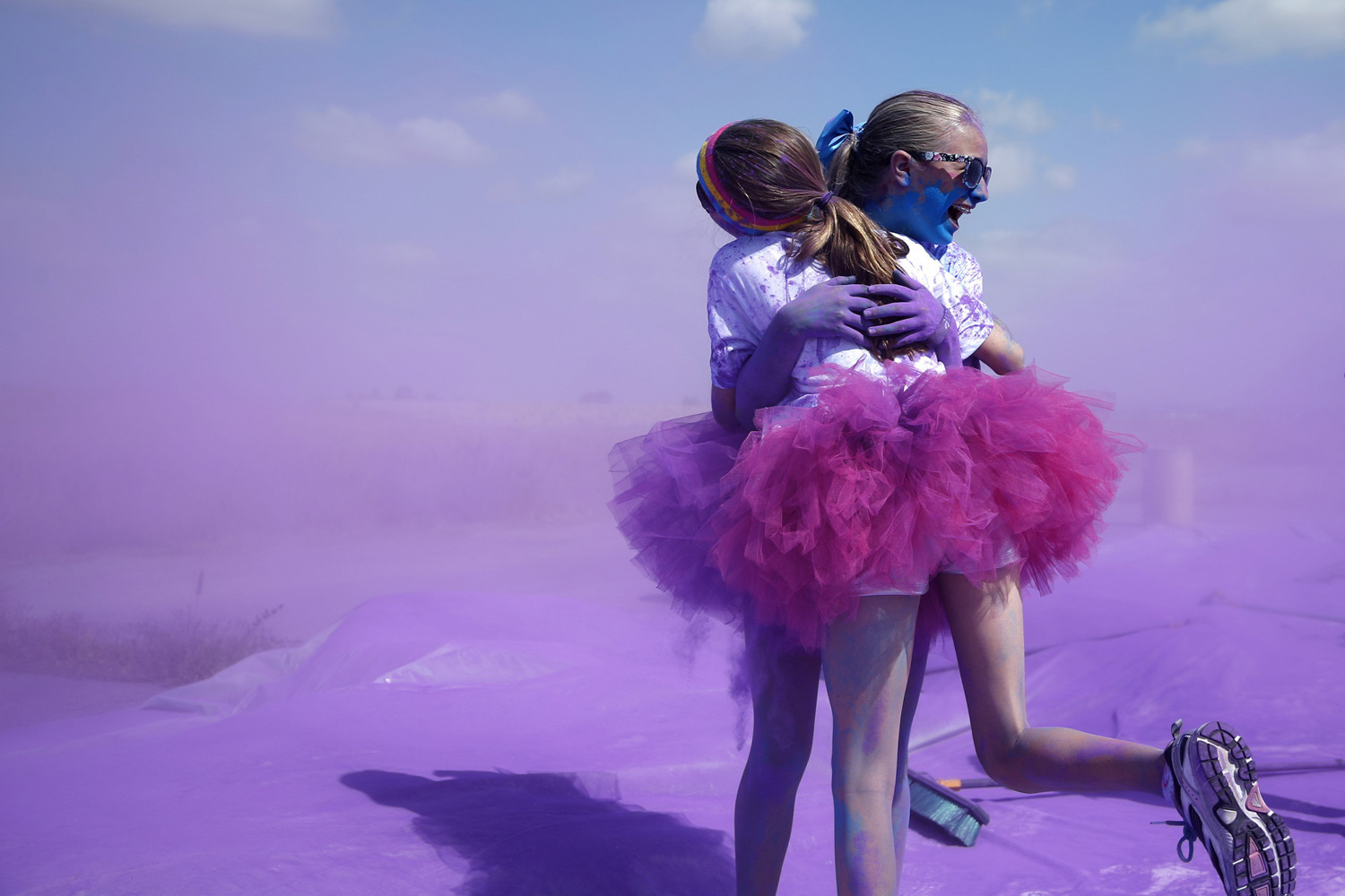 Competitors hug after running through colored powder at the Orange County Color 5K Run in Irvine, Calif., on May 10, 2014.