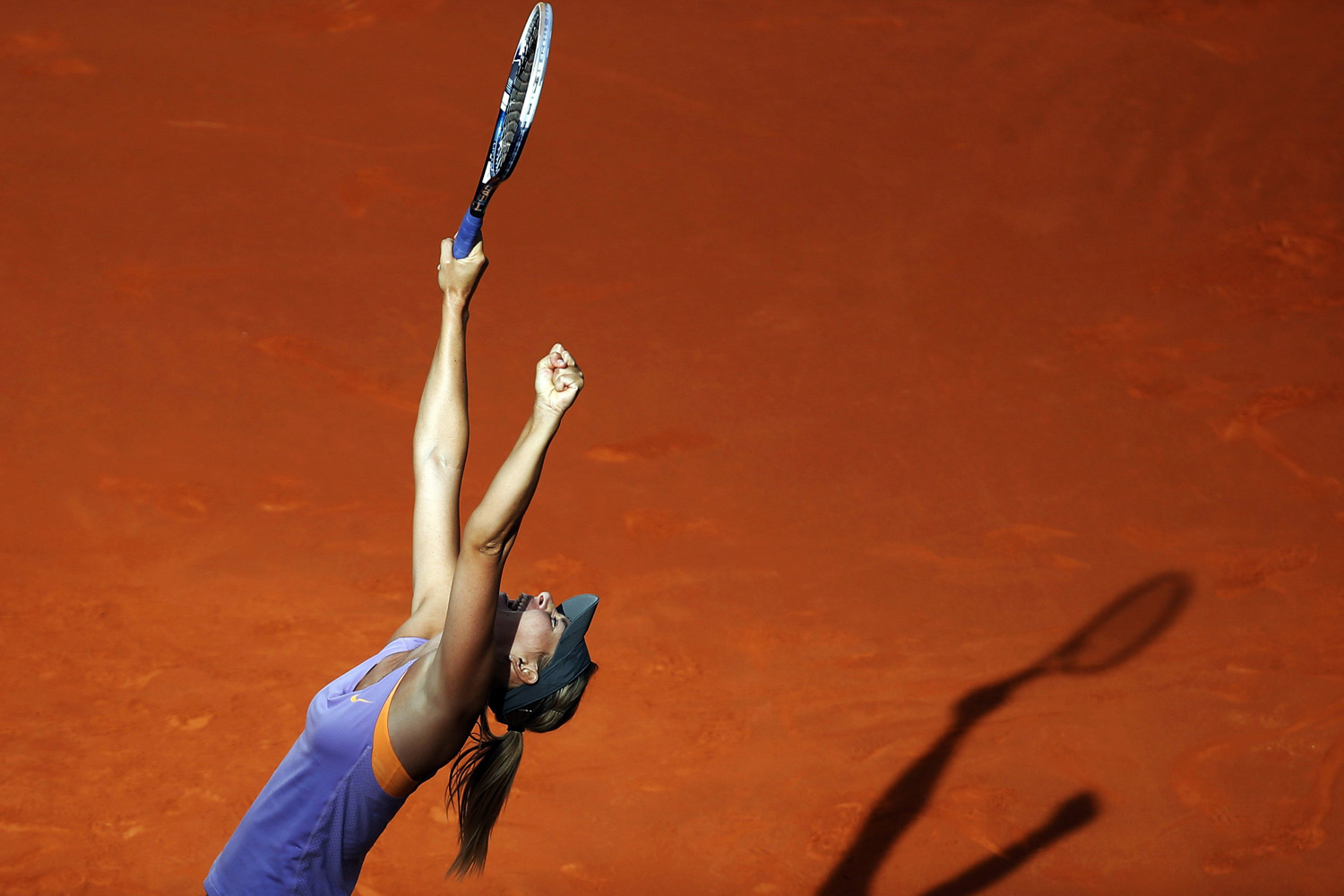 Maria Sharapova of Russia celebrates her victory over Simona Halep of Romania at the end of their women's singles final match at the Madrid Open tennis tournament on May 11, 2014.