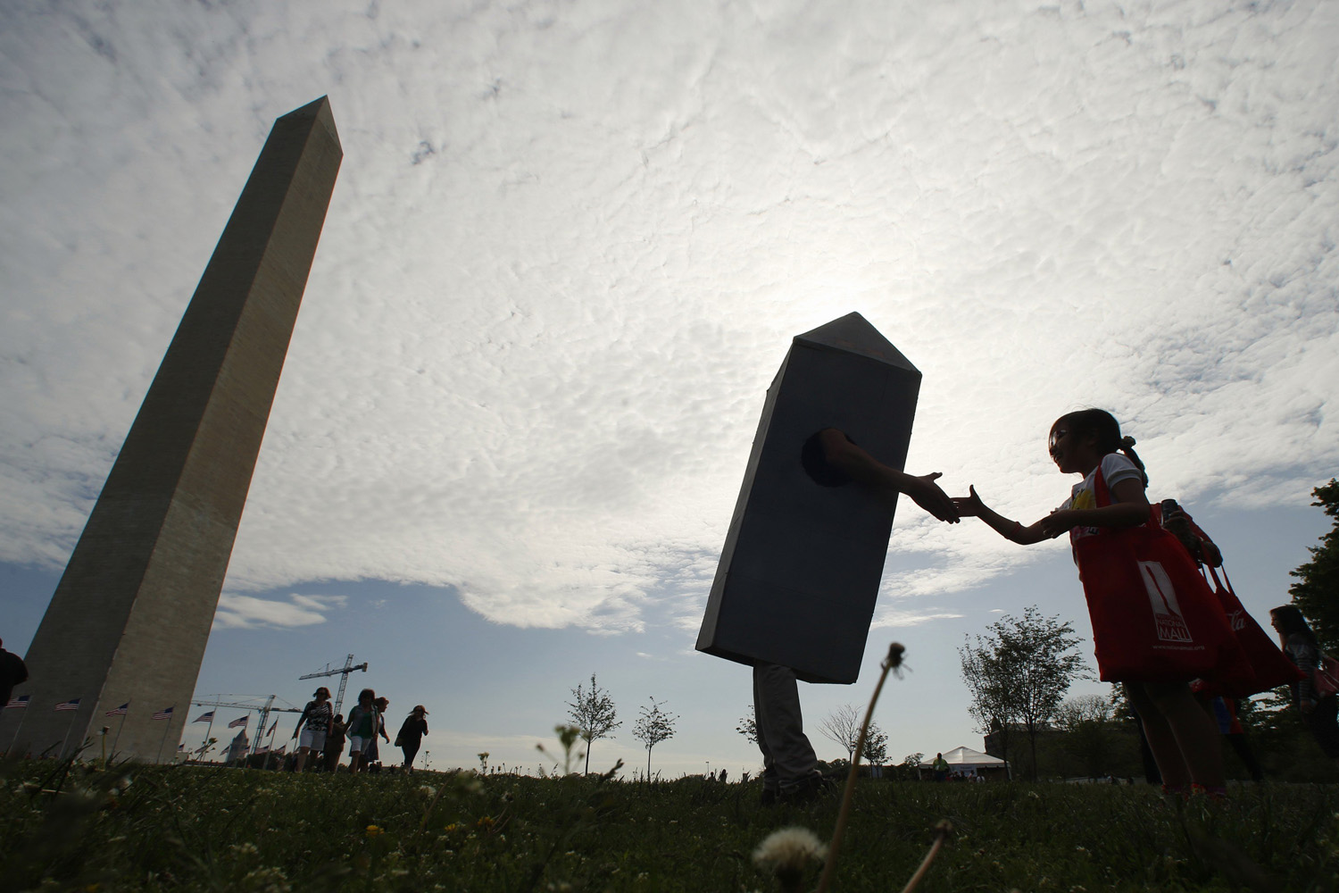 A girl shakes hands with a man dressed as the Washington Monument at the monument's re-opening ceremony in Washington, D.C., on May 12, 2014.