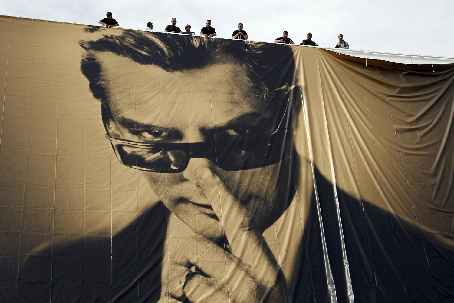 May 12, 2014. Workers set up a giant canvas of the official poster of the 67th Cannes Film Festival featuring actor Marcello Mastroianni on the Festival Palace in Cannes.